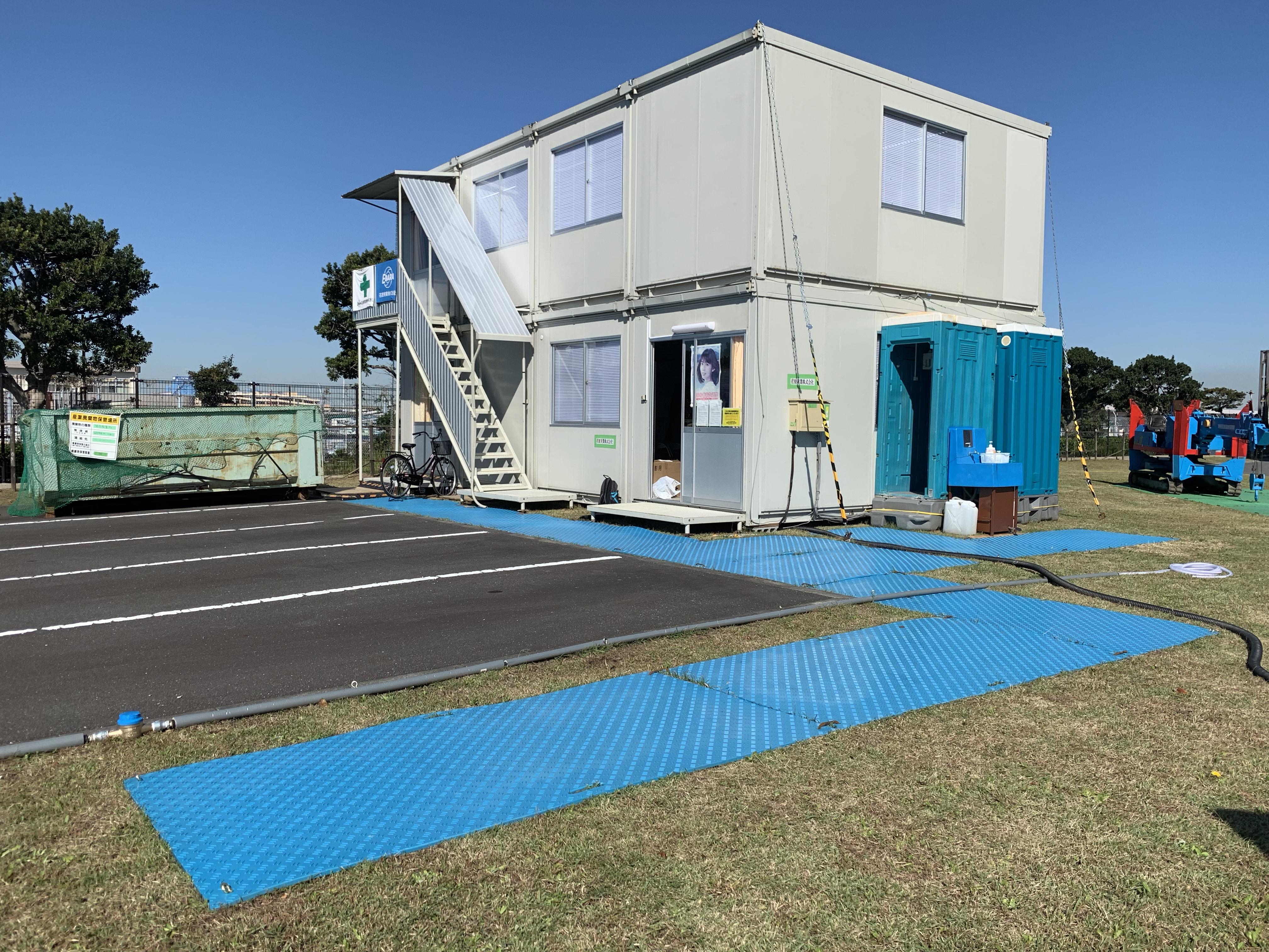 芝生の上に現場事務所を設置。芝生の損傷防止に樹脂敷板を利用