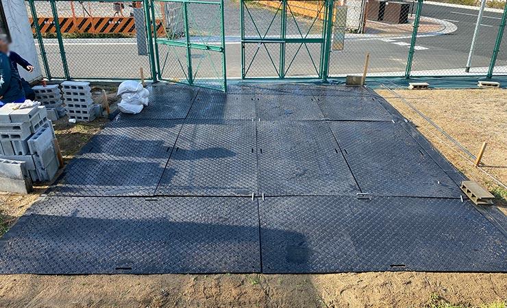 ぬかるむ土地の搬入口にプラスチック敷板を利用